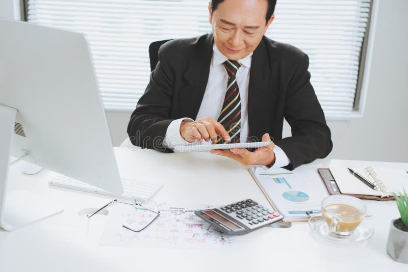 Moget affärsmansammanträde för pensionär på kontoret framme av bärbara datorn royaltyfri bild