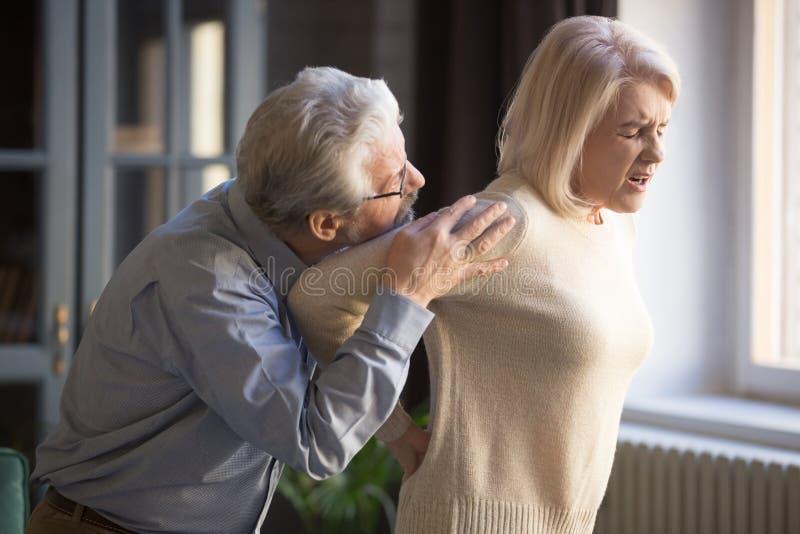 Moget kvinnalidande från den plötsliga ryggvärken, gamal man som stöttar henne arkivfoton