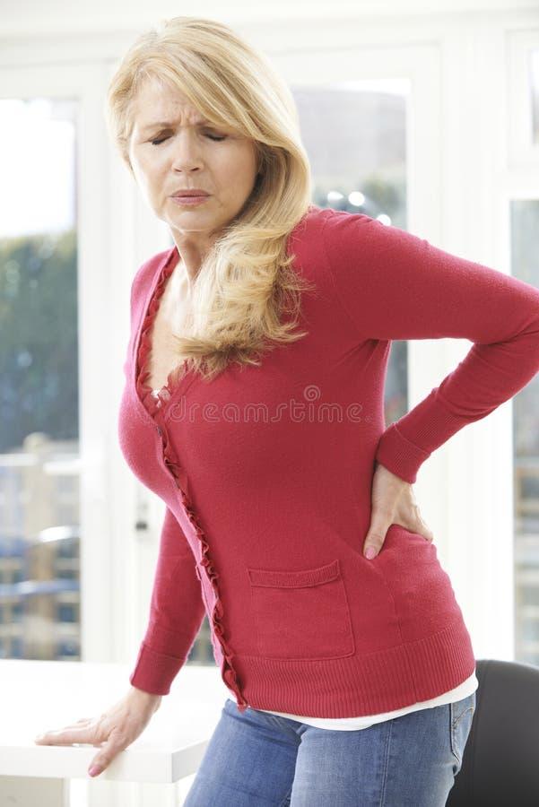 Moget kvinnalidande från ryggvärk hemma royaltyfri foto