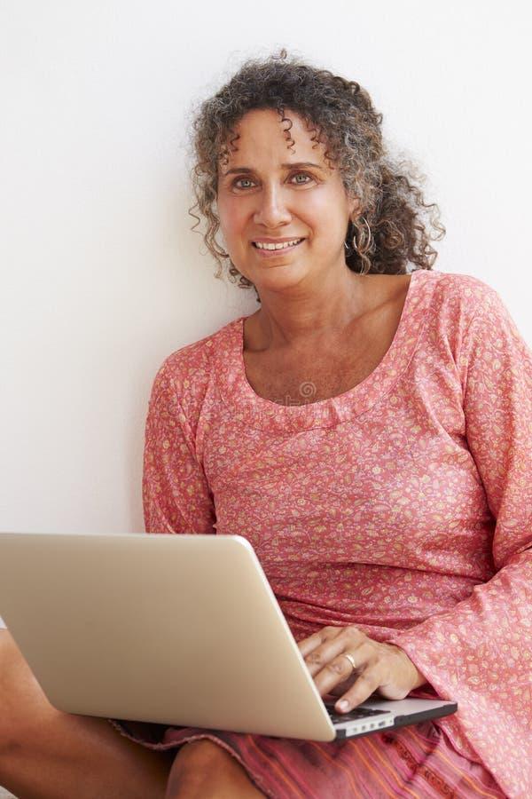 Moget kvinnasammanträde mot väggen genom att använda bärbara datorn arkivbild