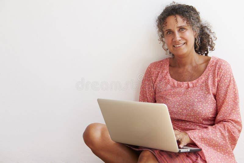 Moget kvinnasammanträde mot väggen genom att använda bärbara datorn arkivfoto