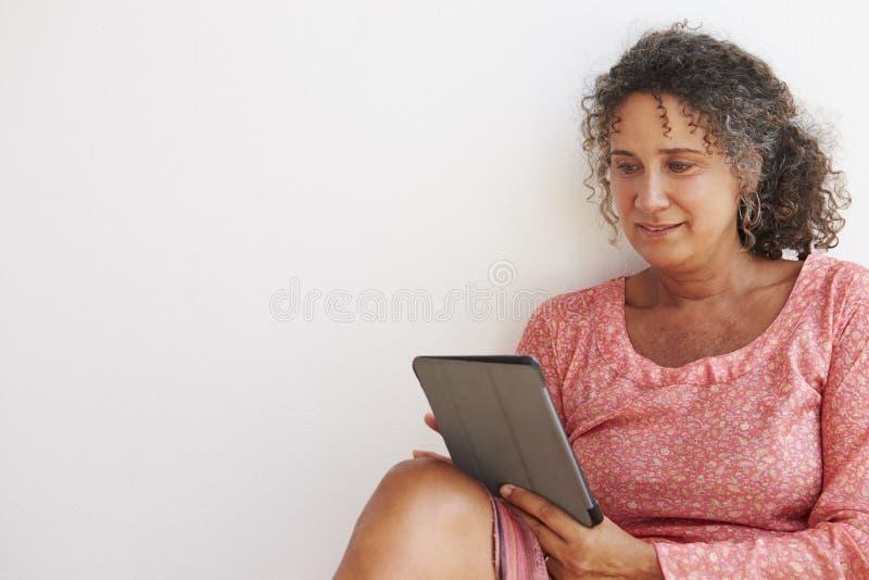 Moget kvinnasammanträde mot väggen genom att använda den Digital minnestavlan royaltyfria bilder