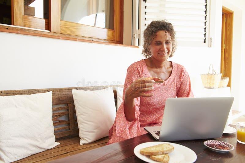 Moget kvinnasammanträde på frukosttabellen genom att använda bärbara datorn fotografering för bildbyråer