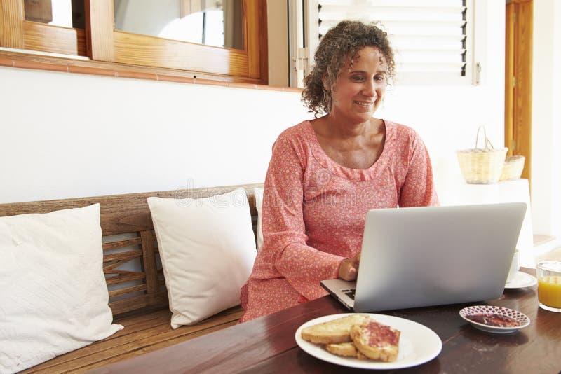 Moget kvinnasammanträde på frukosttabellen genom att använda bärbara datorn arkivfoton