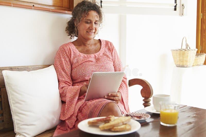 Moget kvinnasammanträde på frukosttabellen genom att använda den Digital minnestavlan royaltyfri fotografi