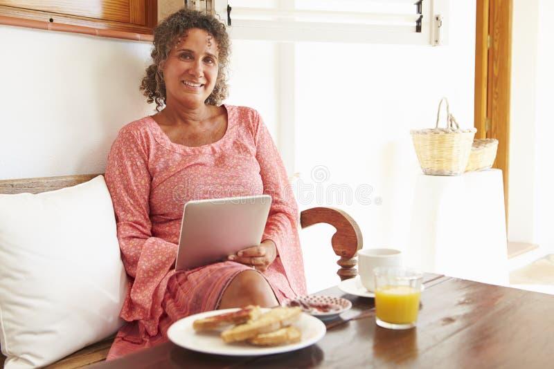 Moget kvinnasammanträde på frukosttabellen genom att använda den Digital minnestavlan royaltyfri foto