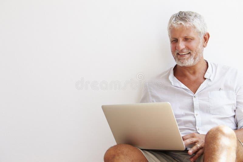 Moget mansammanträde mot väggen genom att använda bärbara datorn arkivfoton