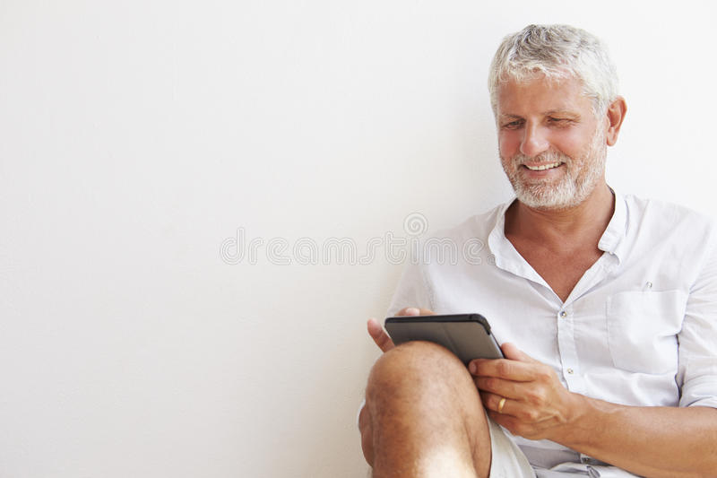 Moget mansammanträde mot väggen genom att använda den Digital minnestavlan royaltyfria bilder