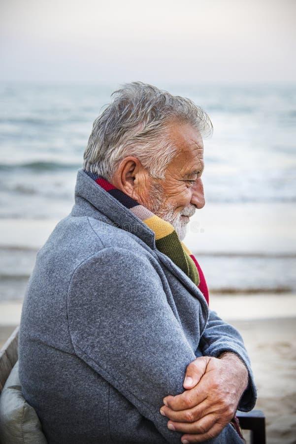 Moget mansammanträde på en stol vid kusten royaltyfri bild