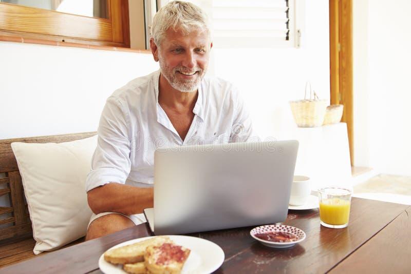 Moget mansammanträde på frukosttabellen genom att använda bärbara datorn arkivfoton