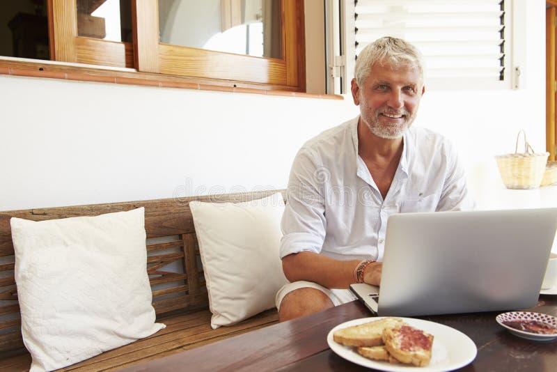 Moget mansammanträde på frukosttabellen genom att använda bärbara datorn arkivbild
