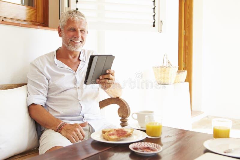 Moget mansammanträde på frukosttabellen genom att använda den Digital minnestavlan royaltyfri bild