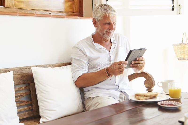 Moget mansammanträde på frukosttabellen genom att använda den Digital minnestavlan arkivfoto
