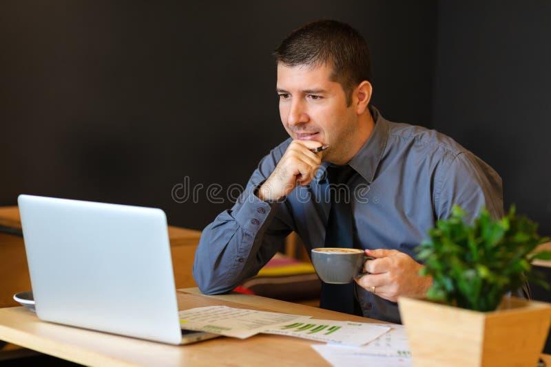 Moget mellersta - östlig man med innehavkopp kaffearbete på bärbara datorn på det moderna kafét som analyserar skatter royaltyfria foton