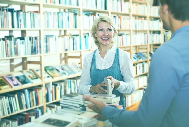 Moget positivt kvinnaanseende bland bokhyllor royaltyfria foton