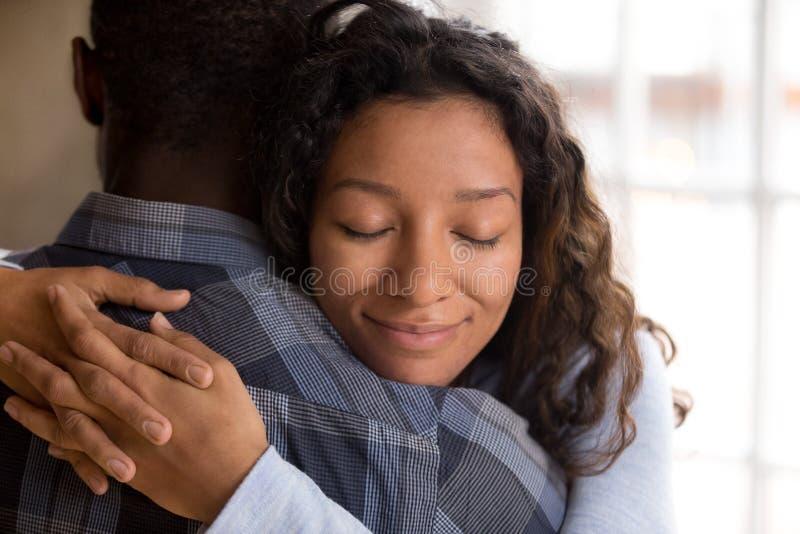 Moglie afroamericana felice che abbraccia marito che tiene feelin stretto fotografia stock libera da diritti