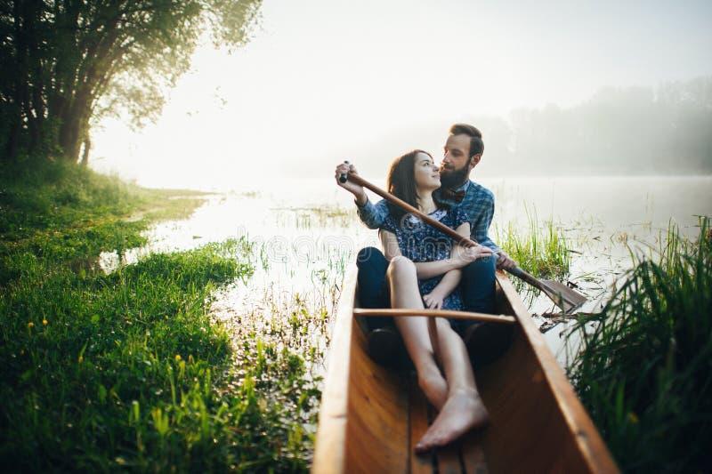 Moglie con il marito che si siede in canoa nella mattina fotografia stock libera da diritti