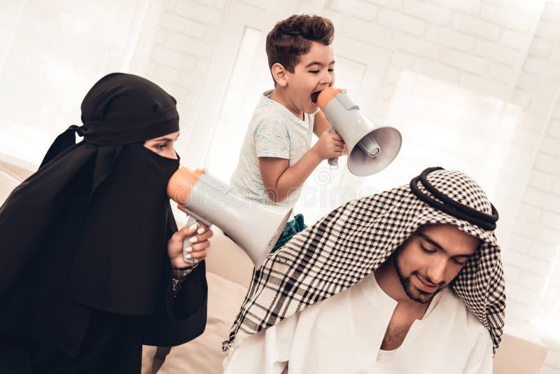 Moglie e figlio con gli altoparlanti che gridano per generare fotografia stock