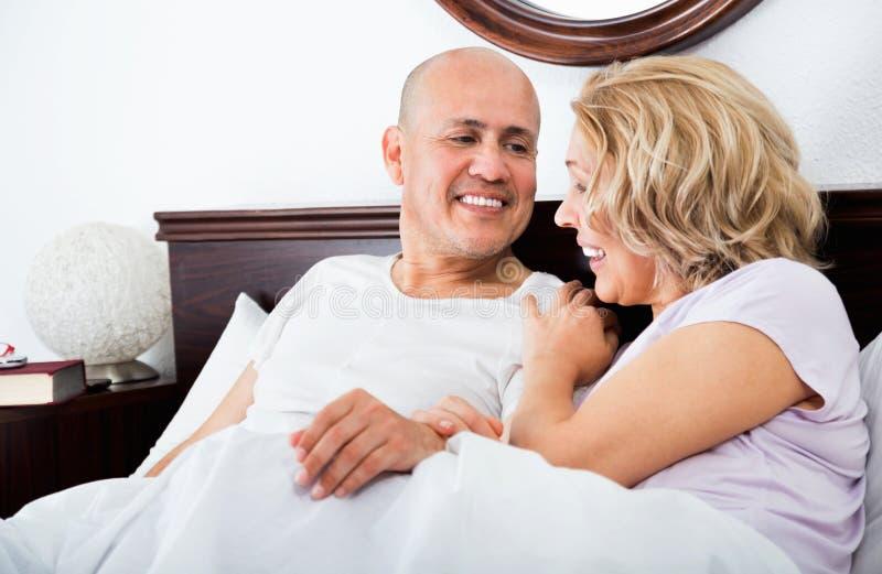 Mogna älska par som är slö i säng, når du har vaknat kel royaltyfri bild