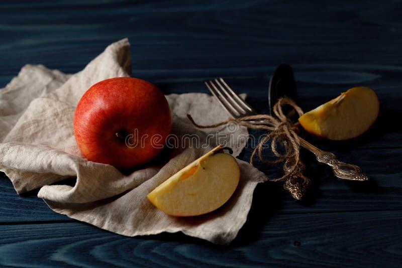 Mogna äpplefrukter och kniv på den gamla trätabellen med kanfas royaltyfri bild