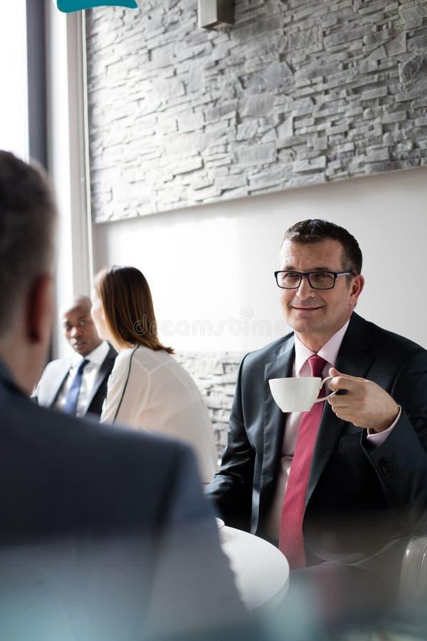 Mogna affärsmannen som har kaffe, medan sitta med den manliga kafeterian för kollegan i regeringsställning royaltyfri bild