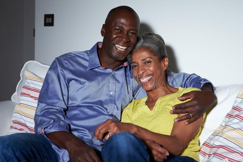 Mogna afrikansk amerikanpar på Sofa Watching TV tillsammans fotografering för bildbyråer