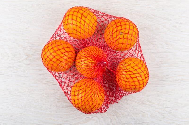Mogna apelsiner i rött ingrepp på trätabellen royaltyfria foton