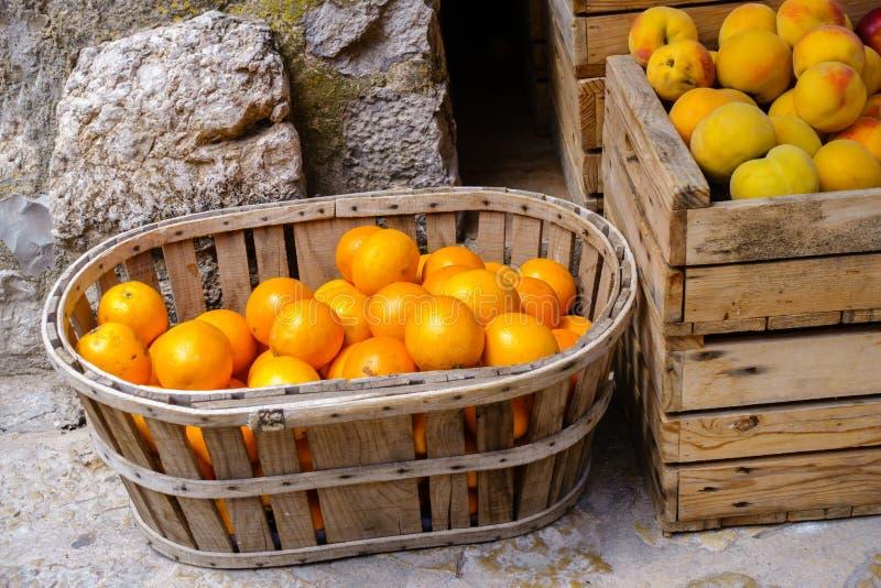 Mogna apelsiner och persikor i träask och korg på en matmarknad royaltyfria foton