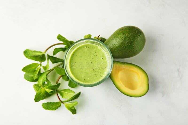 Mogna avokadon, mintkaramell och exponeringsglas av den smakliga smoothien på ljus bakgrund arkivfoto