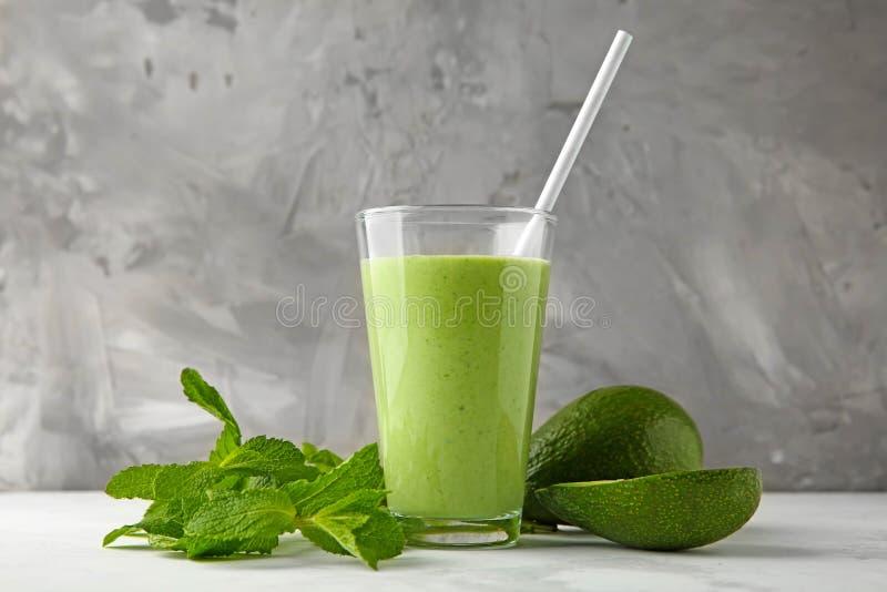 Mogna avokadon, mintkaramell och exponeringsglas av den smakliga smoothien på tabellen royaltyfria bilder