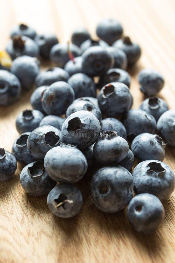 Mogna beströdda blåbär på en trätabell, vertikalt royaltyfria bilder