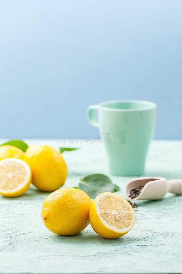 Mogna citroner och en kopp te på enblått bakgrund royaltyfria foton
