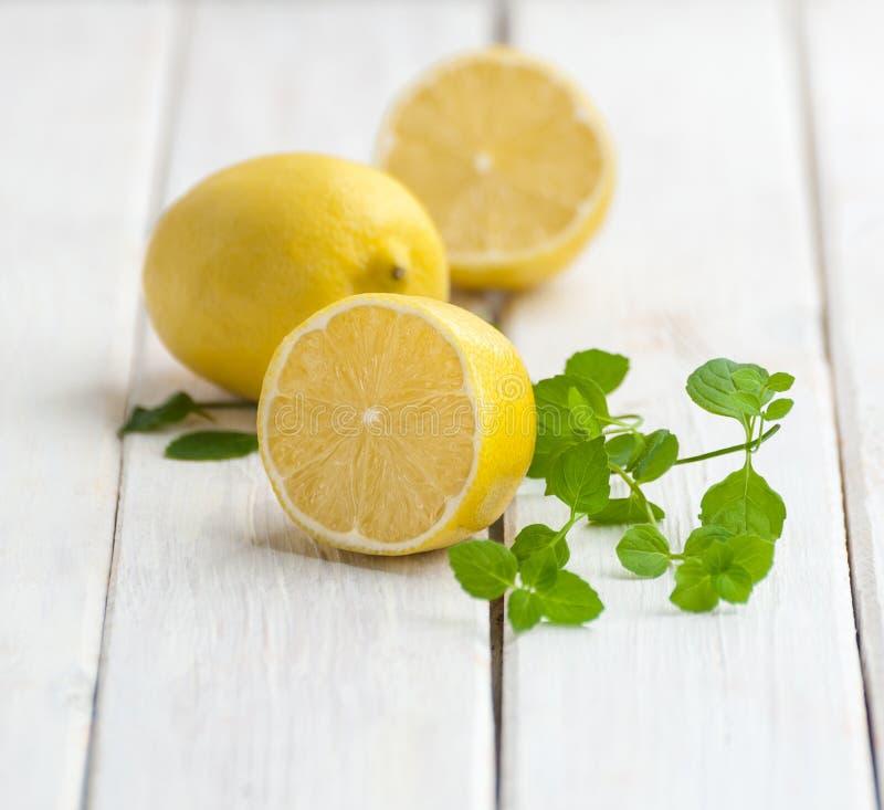 Mogna citroner och en mintkaramell förgrena sig på en vit trätabell royaltyfri fotografi