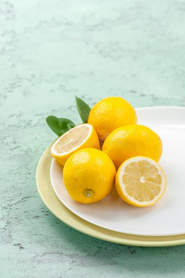 Mogna citroner på en platta på enfärgad tabell arkivfoto