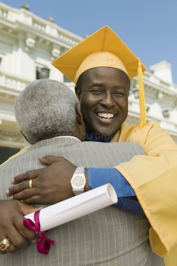 Mogna den doktorand- krama fadern royaltyfria bilder
