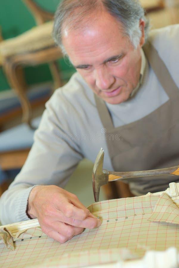Mogna den kompetenta arbetaren som reparerar stol royaltyfri fotografi