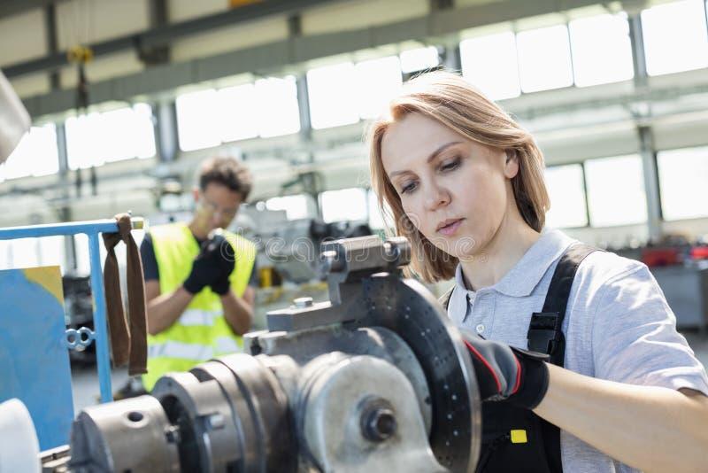 Mogna den kvinnliga arbetaren som arbetar på maskineri med kollegan i bakgrund på bransch arkivbilder