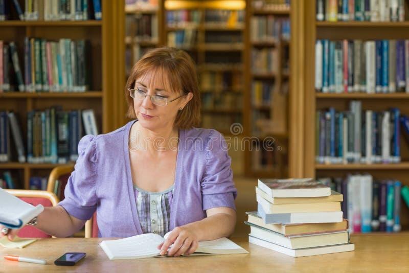Mogna den kvinnliga studenten som studerar på skrivbordet i arkivet royaltyfri bild