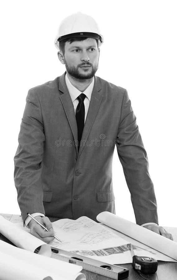 Mogna den manliga arkitekten som tänker, medan arbeta på en ritning arkivbild