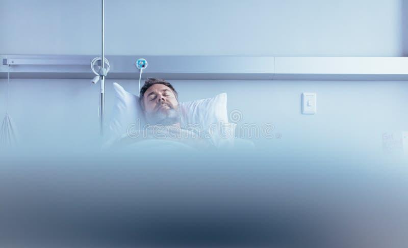 Mogna den sjuka manliga patienten som sover i sjukhussäng royaltyfria bilder