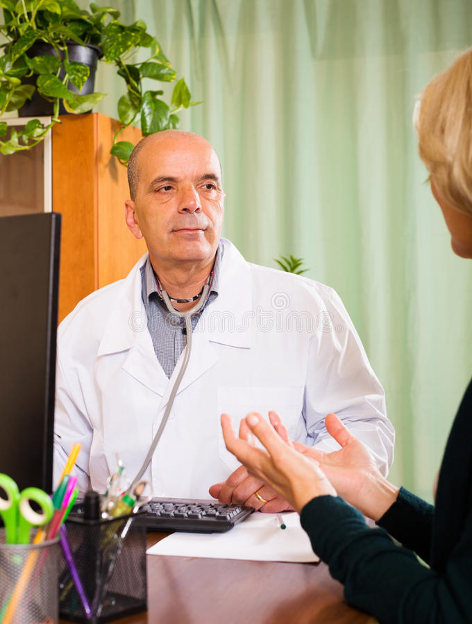 Mogna doktorn som lyssnar med den kvinnliga patienten i klinik royaltyfri fotografi