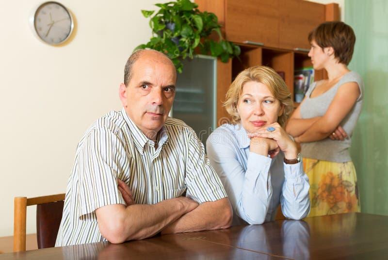 Mogna föräldrar med dottern som har konflikt arkivfoton