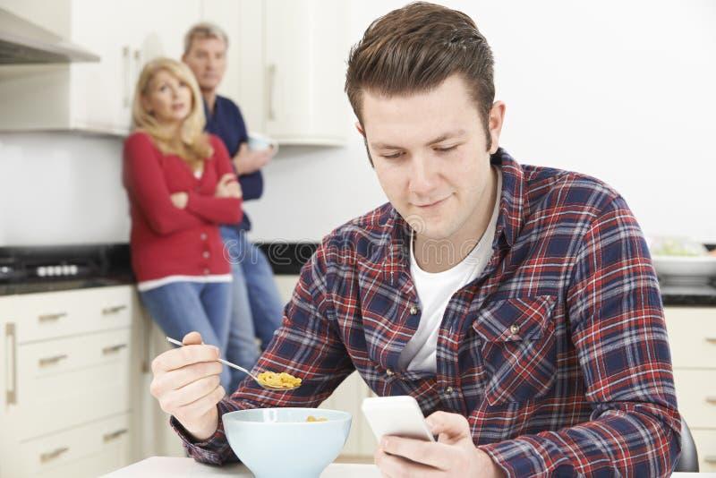 Mogna föräldrar som frustreras med den vuxna sonen som hemma bor royaltyfria bilder