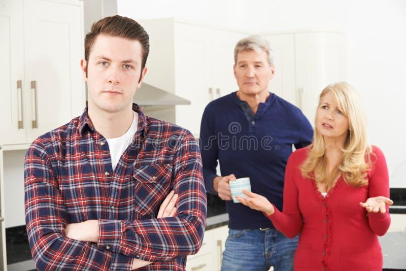 Mogna föräldrar som frustreras med den vuxna sonen som hemma bor royaltyfria foton