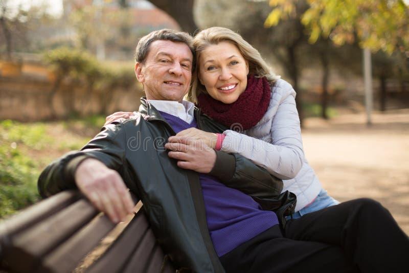 Mogna familjpar på en bänk i parkera i höstdag arkivbilder