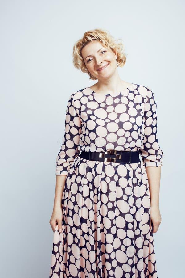 Mogna gladlynt posera för blond lockig kvinna på isolerad vit bakgrund, livsstilfolkbegrepp royaltyfria bilder