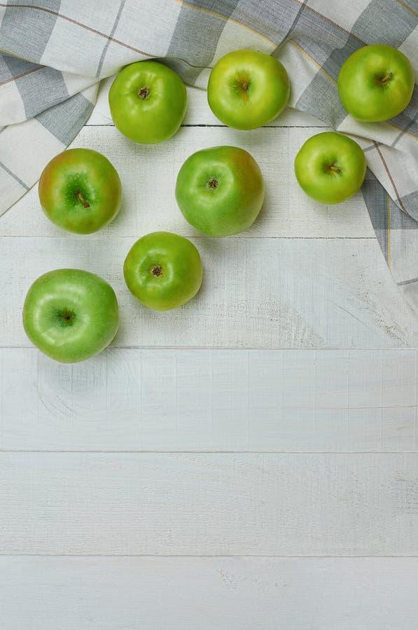 Mogna gröna äpplen på ljus träbakgrund royaltyfri bild
