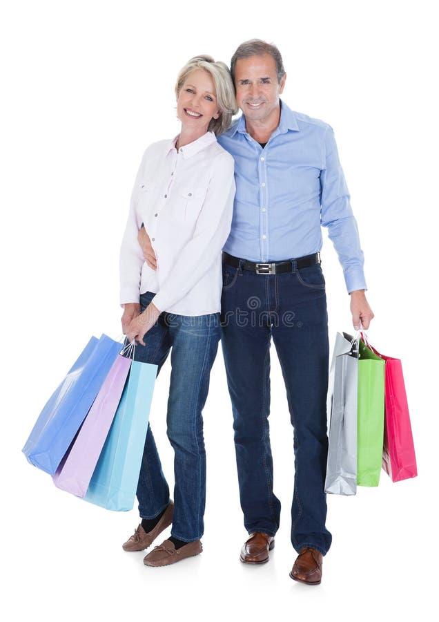 Mogna hållande shoppingpåsar för par royaltyfri fotografi