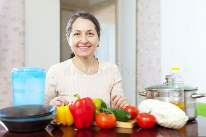 Mogna hemmafrun med grönsaker på kök royaltyfria foton