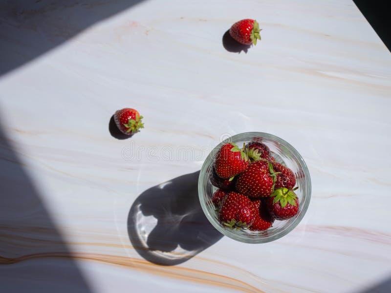 Mogna jordgubbar i en exponeringsglaskopp på en marmortabell royaltyfri foto